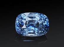 Luxury blue transparent sparkling gemstone shape cushion cut sapphire isolated on black background stock image