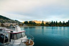 Luxury boat dock in Queenstown New Zealand tourist destination with golden sunset lights on The Remarkables mountains stock photography