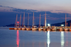 Luxury boats aligned near the dam in night royalty free stock images