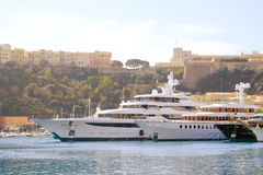Luxury boats in Marina. Luxury boats moored in marina in south of France with Grimaldi Royal Palace on hill in background Royalty Free Stock Photos