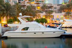 Luxury Boats in the sunset. Luxury Boats berthing in Dubai Marina with waterfront apartments in the background royalty free stock images