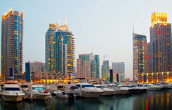 Luxury Boats in the sunset. Luxury Boats berthing in Dubai Marina with luxury waterfront apartments in the background Royalty Free Stock Photos