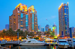 Luxury Boats in the sunset 2. Boats and yachts berthed in the Dubai Marina with luxury apartments in the background Royalty Free Stock Image