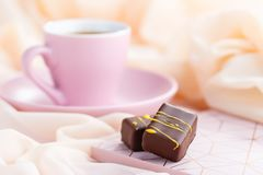Luxury bonbons with cup of coffee on pastel pink background. Exclusive handmade chocolate candy. Springtime, Womans Day, Valentines Day concept Royalty Free Stock Photography