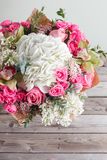 Luxury bouquet of different flowers in glass vase on wooden wall. Copy space Stock Photography