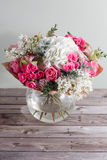 Luxury bouquet of different flowers in glass vase on wooden wall. Copy space Stock Images