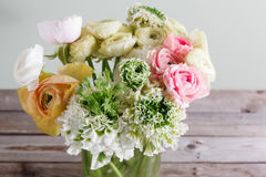 Luxury bouquet of different flowers in glass vase on wooden wall. Copy space Stock Photos