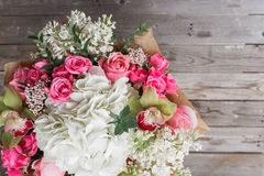 Luxury bouquet of different flowers in glass vase on wooden wall. Copy space Stock Photo