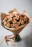 Luxury bouquet of tiny roses laying on wooden table in cafe between coffee cappuccino and glass  vine, film like colors Royalty Free Stock Images