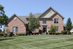 Luxury brick home in suburbs. With manicured lawn Royalty Free Stock Photography