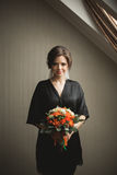 Luxury bride in black robe posing while preparing for the wedding ceremony Stock Images