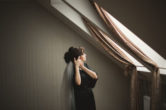Luxury bride in black robe posing while preparing for the wedding ceremony Stock Image