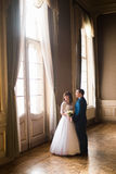 Luxury bride and handsome groom holding hands at gorgeous window on the background of rich interior in old building Stock Photo