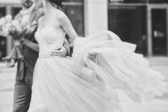 Luxury bride holding a flying dress and walking Royalty Free Stock Photos