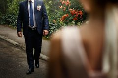 Luxury bride looking at her groom walking, gorgeous pink and white bouquet, rich wedding couple, tender romantic moment at garden. With blossoms royalty free stock image