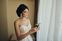Luxury bride in vintage dress with bouquet posing in luxury hote. Beautiful bride with a bouquet of flowers in the hotel room Royalty Free Stock Photos