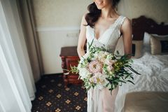 Beautiful bride with a bouquet of flowers in the hotel room stock photography