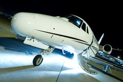 Luxury business jet on a runaway. Ready for boarding with open doors and stairs down at night royalty free stock photos