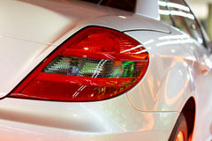 Luxury car. Details of  luxury car's stoplight with colored reflections Stock Photos