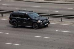 Luxury car black Mercedes  Benz GL speeding on empty highway Stock Photos