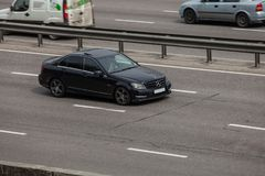 Luxury car black Mercedes  Benz  speeding on empty highway Royalty Free Stock Photos