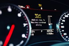 Luxury car color screen dashboard with warning message. Low engine oil level indication. Intelligent Driver Information System. Red display light panel sign royalty free stock image