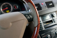 Luxury car interior. With wooden steering wheel close up Royalty Free Stock Photo