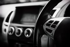 Luxury car interior details. Middle console with air and multimedia controls soft focus in black and white concept stock photos
