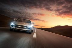 Luxury car. Luxury sports car speeding on empty highway at the sunset
