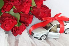 Valuable present for someone special concept. Wedding background. Luxury car tied up with a red ribbon with a bow on the roof as a gift and a bouquet of red Royalty Free Stock Images
