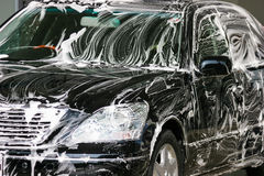 Luxury Car Wash. Black luxury sedan with suds being washed by hand in the sunshine Stock Image