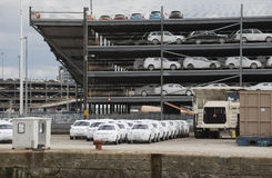 Luxury cars wrapped for protection await export at docks Stock Photos
