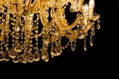 Luxury chandelier with light candles and right dark background. Noble candelabra hanging on ceiling with lots of little gems Royalty Free Stock Images
