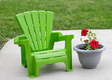 Luxury Childrens Chair. A green child sized adirondack chair next to a planter on a concrete terrace.  Kids like to relax these days too.  This would look great Stock Image