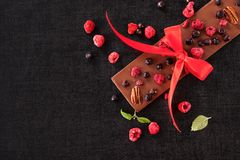 Chocolate bar with freeze-dried berries. Luxury chocolate bar with ribbon and healthy freeze-dried berries from above with copy space royalty free stock image