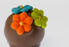 Luxury Chocolate. Milk chocolate covered truffle decorated with icing flowers Royalty Free Stock Images