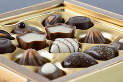Luxury chocolates. Luxury chocolate assortment in a gold box Royalty Free Stock Photography