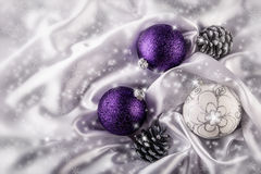 Luxury Christmas Balls Silver Pine Cones On White Satin Christmas Decoration Combined Purple And Silver Colors. Stock Image