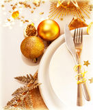 Luxury Christmas table setting. Image of luxury Christmas table setting, festive white dishware served with silver cutlery and decorated with beautiful golden Stock Photography