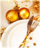 Luxury Christmas table setting. Image of luxury Christmas table setting, festive white dishware served with silver cutlery and decorated with beautiful golden Stock Photo