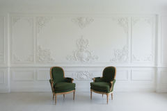 Luxury clean bright white interior with a old antique vintage green chairs over wall design bas-relief stucco mouldings Stock Photography