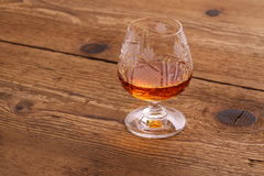 Luxury Cognac in decorated crystal glass on wood Stock Photos