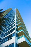 Luxury Condominium High Rise. Modern, luxury condominium high rise located in Miami Beach, Florida. Taken from low perspective upward. Against a blue, cloudless stock photography