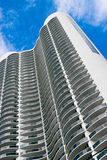 Luxury Condominium High Rise. Modern, luxury condominium high rise located in Sunny Isles, Florida. Taken from low perspective upward. Against a blue sky stock image