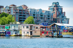 Luxury condominiums tower over colorful house boats. Moored at Fisherman's Wharf in Victoria, British Columbia Royalty Free Stock Photo