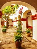 Luxury country house. Beautiful arch decorated with fresh flowers and trees, comfortable cottage, expensive landscaping design, traditional mexican exterior Stock Photo