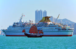 Luxury cruise and chinese junk. A luxury cruise and chinese junk moving along kowloon, hong kong Stock Image