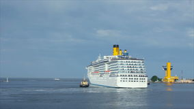A luxury cruise ship leaving port with two tugs assistance time lapse Royalty Free Stock Photo