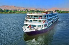 Luxury cruise ship sailing down the river nile. River Nile, Egypt, 2013. A luxury Cruise Ship floating down the nile. Cruise ships are a popular way for tourists royalty free stock photos