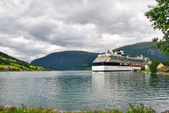 Luxury Cruise Ship Sailing from Port Norway mountains in the background Royalty Free Stock Photos
